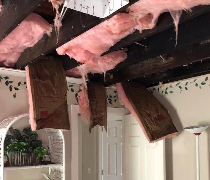 Insulation hanging from the ceiling after a water loss